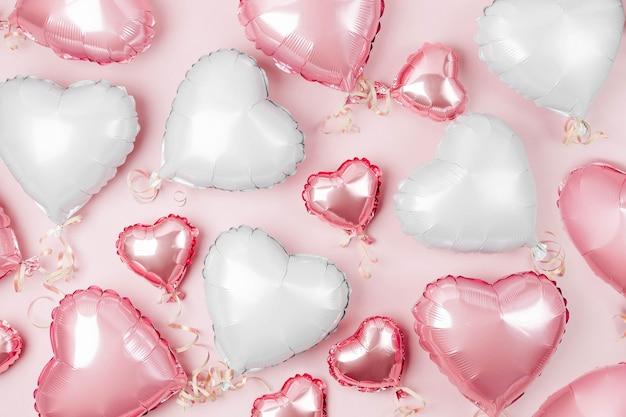 Luftballons aus herzförmiger folie auf pastellrosa hintergrund. liebe konzept. feiertagsfeier. valentinstag oder hochzeits-/junggesellinnenabschiedsdekoration. metallischer ballon