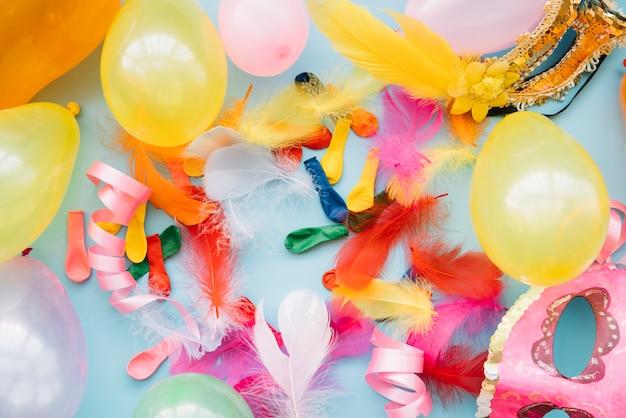 Luftballons in der nähe von masken und federn