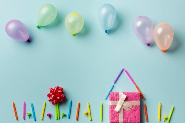 Luftballons über dem haus mit geschenkbox; kerzen und roter bandbogen gegen blauen hintergrund