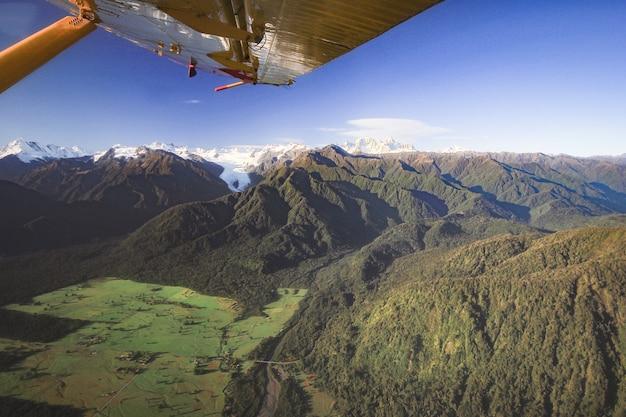 Luftbild auf bergketten und grünen feldern mit flugzeugflügel franz josef neuseeland