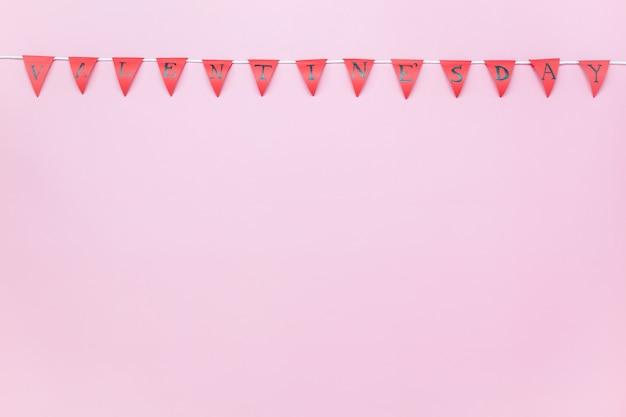 Luftbild der tischplatteansicht des valentinstaghintergrundkonzeptes valentinsgrußflagge oder parteifahne auf modernem rustikalem rosa büroschreibtischstudio der tapete zu hause.
