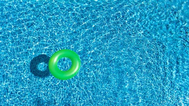 Luftbild des bunten aufblasbaren ringkrapfenspielzeugs im schwimmbadwasser von oben, familienurlaubsferienorthintergrund