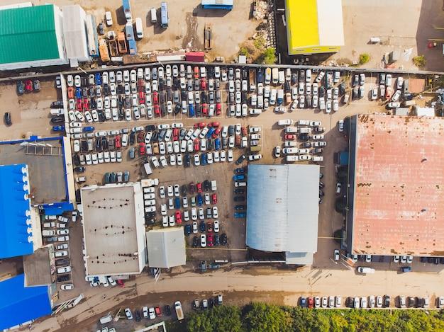 Luftbild eines kleinen temporären autoparkplatzes zur aufbewahrung neuer autos für den wiederverkauf und von autohändlern, die keinen freien platz für die lagerung in großer höhe von oben nach unten haben.