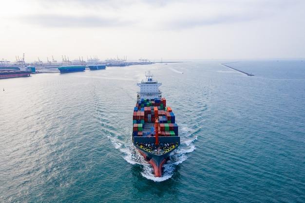 Luftbild frachtschiff des geschäftslogistiktransports seefracht, frachtschiff, frachtcontainer im fabrikhafen im industriegebiet für den import export in der welt, handelshafen / schifffahrt