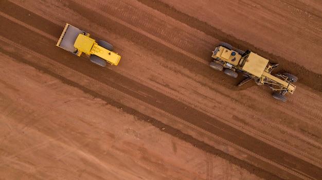 Luftbild gelber bagger, der eine autobahn baut straßengrader schwere erdbewegung bulldozer arbeiten