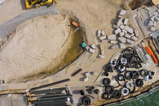 Luftbild rekonstruktion wartung der pier promenade auf einem stapel aus schwarzen pvc-abwasserrohren