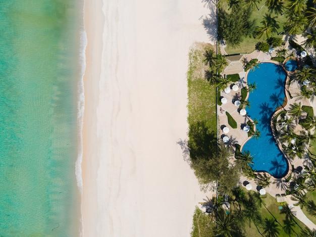 Luftbild urlaubsstrand und schwimmbad im palmenresort.