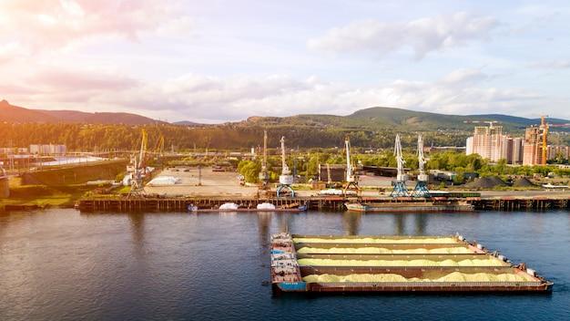 Luftbild von hafenkränen und und lastkahn mit sand über flusshafenlandschaft in der industrie gelegen