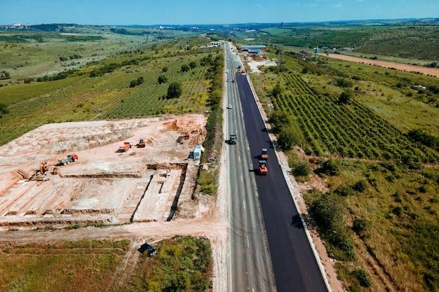 Luftbild von oben auf baustellen mit straßenarbeitern verlegen asphaltarbeiten bei der verlegung von asphaltluftbildern...