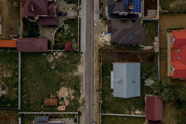 Luftbild von oben auf ein haus mit gepflastertem hof mit grünem rasen mit betonfundament.