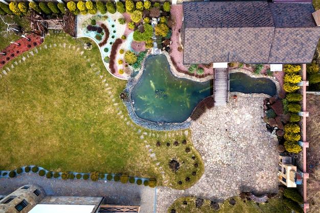 Luftbild von wunderschön angelegten immobilienkomplex. dächer des erholungshaushäuschens, teich im ökologischen bereich am hellen sonnigen tag. moderne architektur, landschaftskonzept.