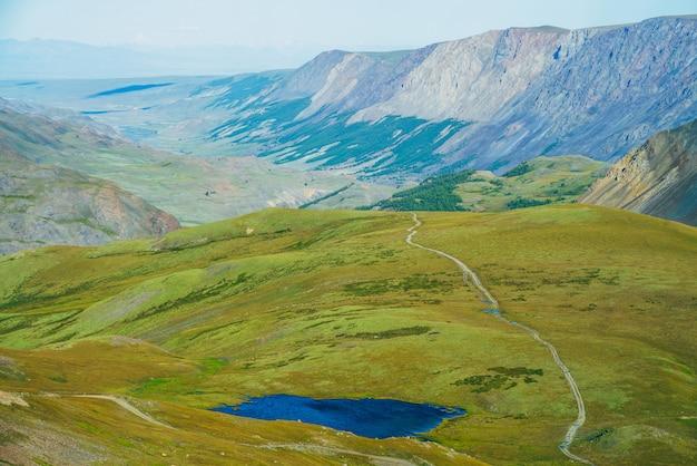 Luftbild zum schönen alpensee mit klarem wasser und langer bergkette im sonnenlicht. fantastische landschaft mit lebendigem blauen see und grünem tal in der ferne am sonnigen tag. bunte hochlandlandschaft.