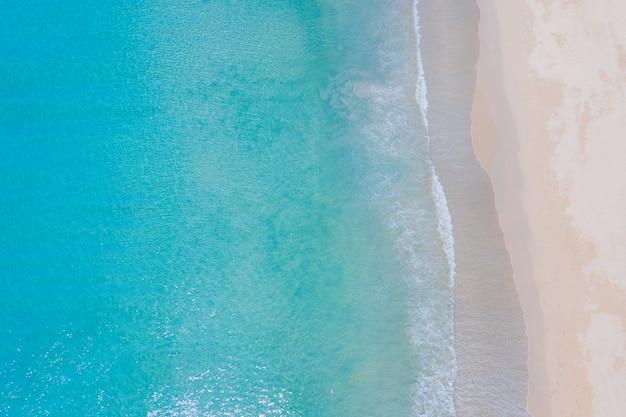 Luftbildaufnahme draufsicht drohnenkamera über strandsand und meerwasser klar