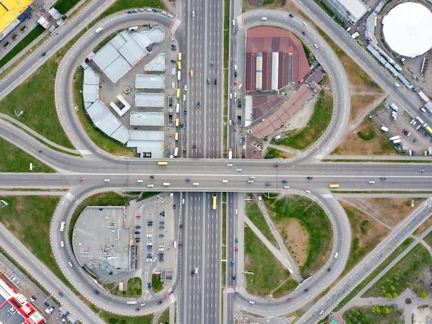 Luftbildbezirk poznyaki, straßenkreuzung mit vorbeifahrenden autos, parkplatz, grünfläche und gebäuden in sity kiew, ukraine. foto von der drohne