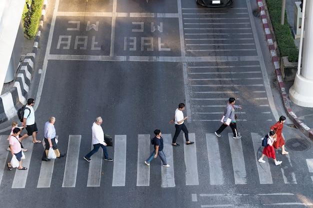 Luftbildfoto von leuten gehen auf straße in der stadt über fußgängerüberwegverkehrsstraße