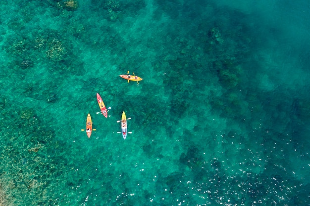 Luftbildgruppe des reisenden, der am strand kayak fährt