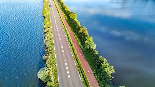 Luftbrummenansicht der autobahnstraße und des radwegs auf polderdamm, autoverkehr von oben, nordholland, die niederlande