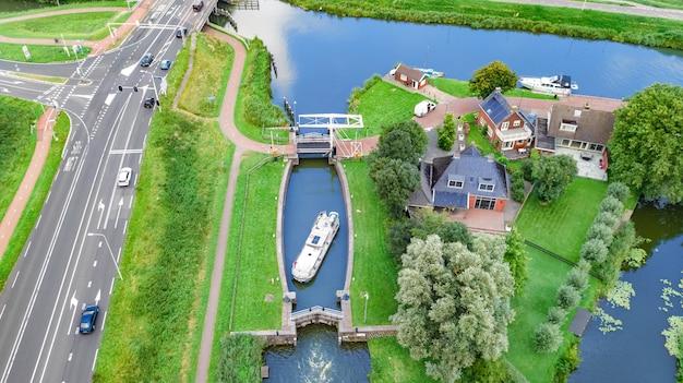 Luftbrummenansicht des hausboots im kanalverschluß, in der landschaft von holland von oben, in der familienreise mit dem lastkahnboot und in den ferien in den niederlanden