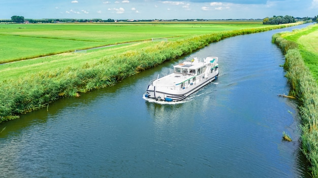 Luftbrummenansicht des hausboots in der kanal- und landlandschaft von holland von oben, familienreise durch lastkahnboot und ferien in den niederlanden