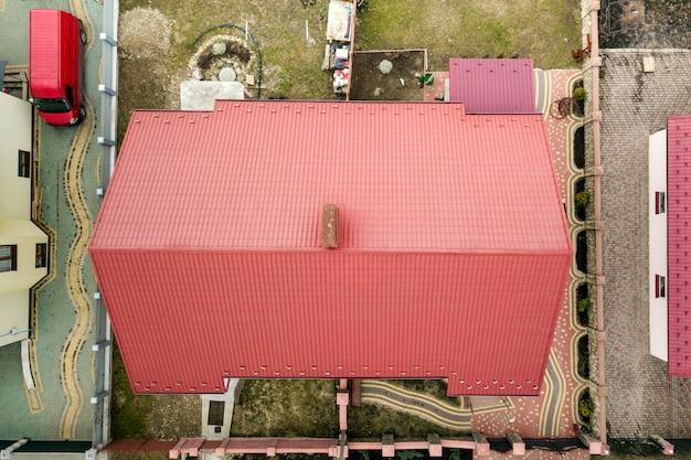 Luftdraufsicht des hausmetallschindeldachs auf eingezäuntem yardhintergrund. dachdecker-, reparatur- und renovierungsarbeiten.
