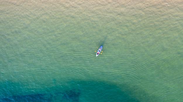 Luftdraufsicht des kayakfahrens um meer mit smaragdblauem wasser des schattens und wellenschaum
