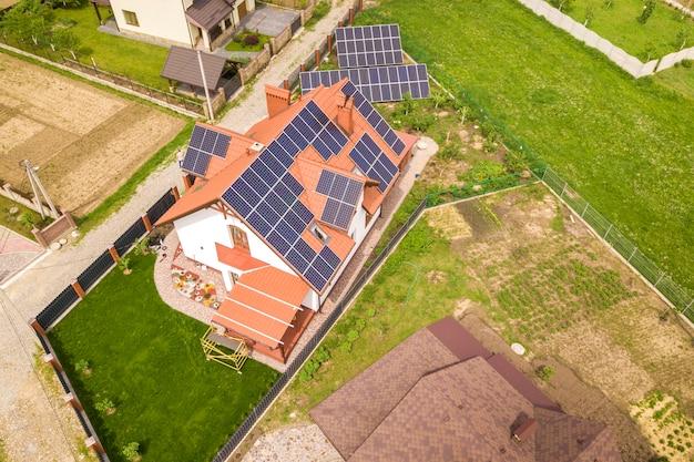 Luftdraufsicht des neuen modernen wohnhaushäuschens mit blauem glänzendem solarpaneelsystem des fotos voltaic auf dach. erneuerbare ökologische ökostrom-produktionskonzept.