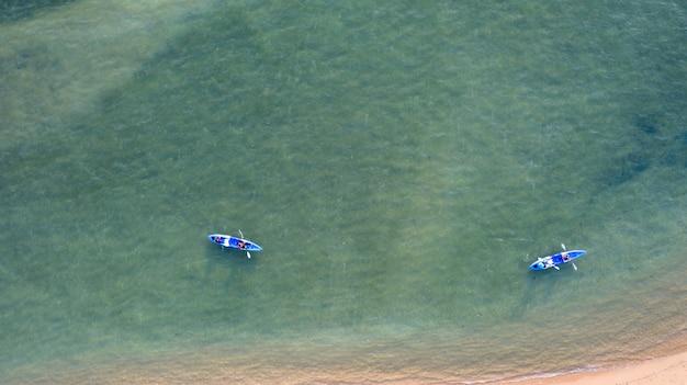 Luftdraufsicht von kayak fahren um meer mit blauem wasser des smaragdwassers und wellenschaum