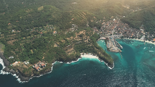 Luftdrohne draufsicht auf den hafenhafen der tropischen insel crystal ocean und die grünen waldberge