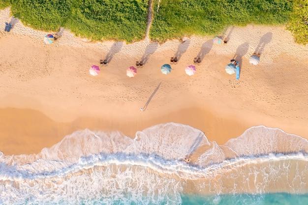 Luftdrohne draufsicht menge glücklicher menschen entspannen sich am tropischen strand mit sonnenuntergang in phuket, thailand, der schöne strand von phuket ist ein berühmtes touristenziel an der andamanensee. ferien-sommer-konzept