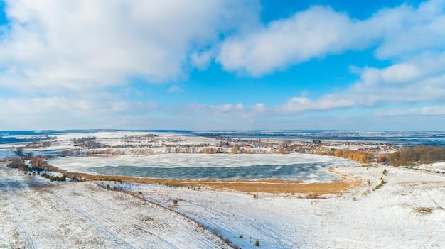 Luftdrohne-fotografie eines teilweise gefrorenen sees umgeben mit schönen winterfarben der felder und des waldes