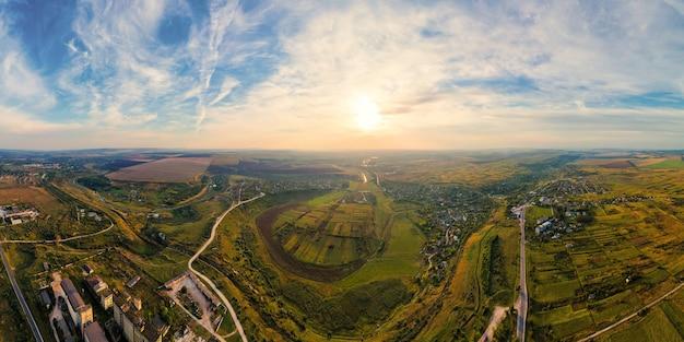 Luftdrohne panoramablick auf die natur in moldawien bei sonnenuntergang. dorf, hügel, weite felder