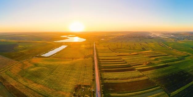 Luftdrohne panoramablick auf die natur in moldawien bei sonnenuntergang. dorf, straße, weite felder, seen