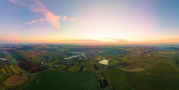Luftdrohne panoramablick auf die natur in moldawien bei sonnenuntergang. dorf, weite felder, see