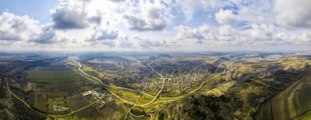 Luftdrohnen-panoramaansicht eines dorfes nahe einem fluss und hügeln, feldern, godrays, wolken in moldawien