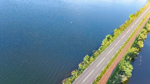 Luftdrohnenansicht der autobahnstraße und des radweges auf polderdamm, autoverkehr von oben, nordholland, niederlande