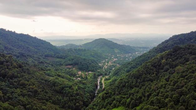 Luftdrohnenansicht der natur im georgia valley mit schmalen fluss- und dorfhügelhängen
