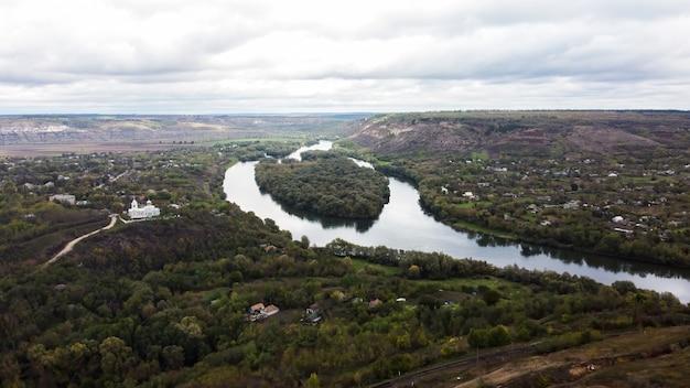 Luftdrohnenansicht der natur in moldawien, schwimmender fluss mit reflektierendem bewölktem himmel und dorf nahe ihm, hügel mit bäumen