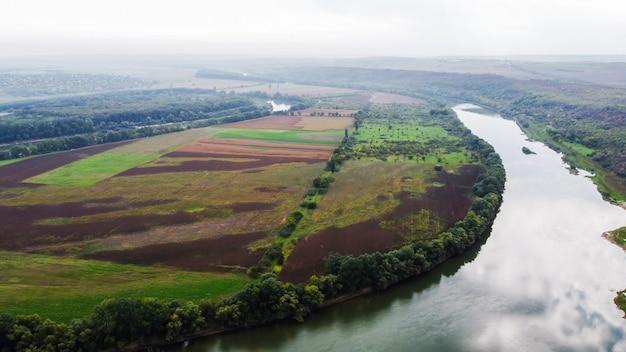 Luftdrohnenansicht der natur in moldawien, schwimmender fluss mit reflektierendem himmel, grüne felder mit bäumen, nebel in der luft