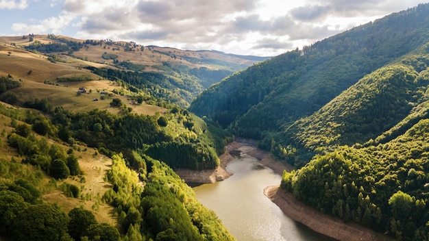 Luftdrohnenansicht der natur in rumänien. hügel, üppiges grün, tal mit fluss, wenige gebäude