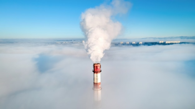 Luftdrohnenansicht der röhre der wärmestation sichtbar über den wolken mit rauch, der herauskommt.