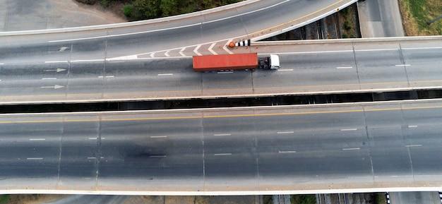Luftdrohnenansicht des frachtweiß-lkws auf der autobahn mit grünem container, transportkonzept, import, exportlogistik industrietransport landverkehr auf der asphaltschnellstraße