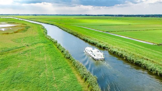 Luftdrohnenansicht des hausboots in der kanal- und landlandschaft von holland von oben, familienreise durch lastkahnboot und urlaub in den niederlanden