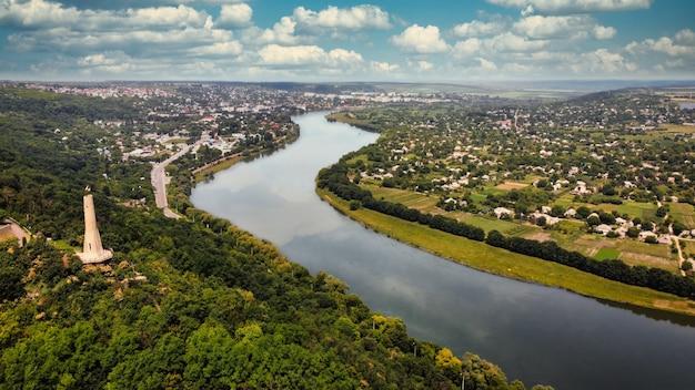 Luftdrohnenansicht einer stadt in moldawien. fluss, wohnhäuser, hügel mit üppigem grün