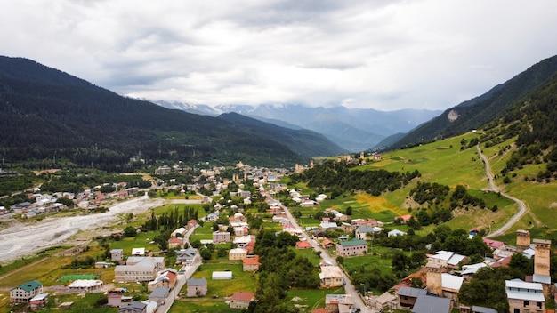 Luftdrohnenansicht eines dorfes in den bergen von georgia valley und den mit grün bedeckten hügelhängen