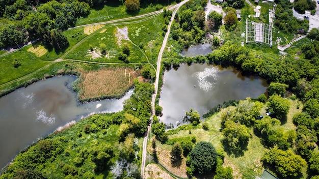 Luftdrohnenansicht eines dorfes in moldawien. landstraße zwischen zwei seen, viel grün