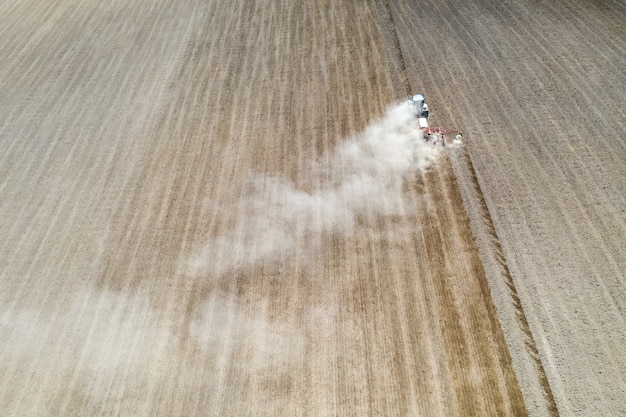 Luftdrohnenansicht mit schöner herbstlandschaft des arbeitstraktors auf dem erntefeld. landwirtschaftskonzept.