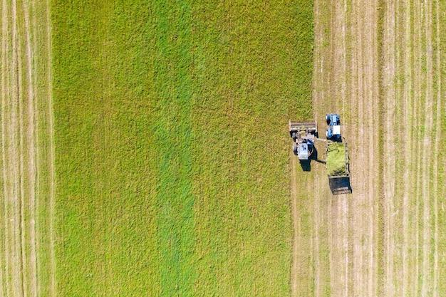 Luftdrohnenansicht mit schöner herbstlandschaft des arbeitstraktors und des mähdreschers auf dem erntefeld. landwirtschaftskonzept.