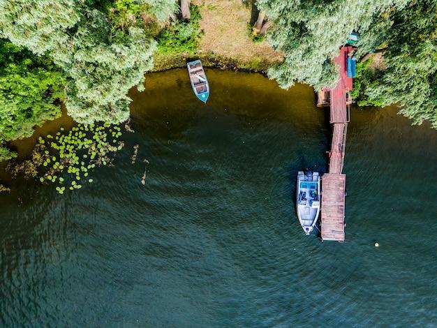 Luftdrohnenansicht von booten, die im sommer am wasser auf dem fluss stehen