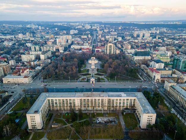 Luftdrohnenansicht von chisinau bei sonnenuntergang. panoramablick auf das stadtzentrum mit dem regierungsgebäude und dem central park, mehreren gebäuden, straßen mit fahrenden autos, kahlen bäumen. moldawien