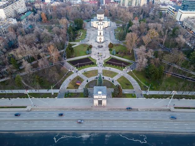 Luftdrohnenansicht von chisinau innenstadt. blick auf den central park mit einer straße. kahle bäume, wandelnde menschen, autos, katheter- und triumphbogen. moldawien